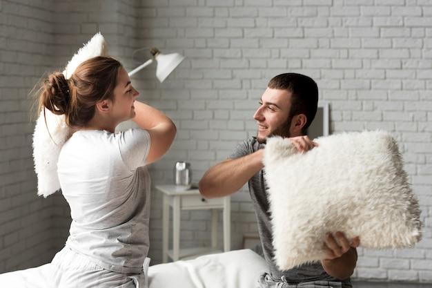 愛らしい若い男性と女性の枕の戦い