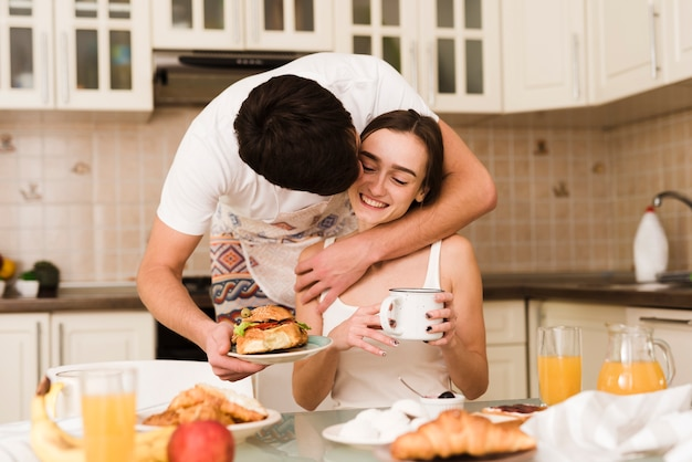 Adorable young man serving breakfast with girlfriend