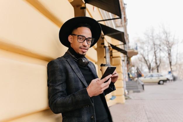 커피 한잔과 함께 오래 된 건물 근처에 갈색 피부 서와 함께 사랑스러운 젊은 남자. 거리에서 포즈를 취하는 동안 전화를 들고 캐주얼 복장에 유행 아프리카 남성 모델.