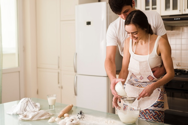 Adorable young man and woman cooking together