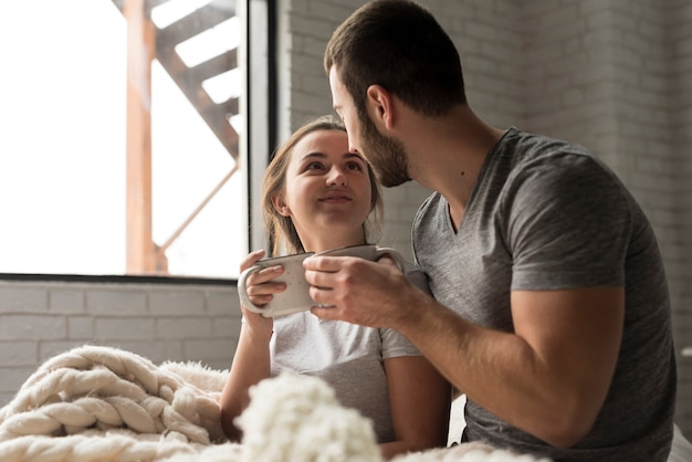 Adorable young man and woman having coffee