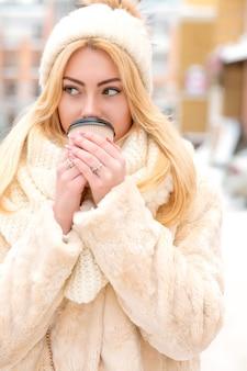 겨울 유행의 옷을 입고 거리에서 커피를 마시는 사랑스러운 젊은 모델