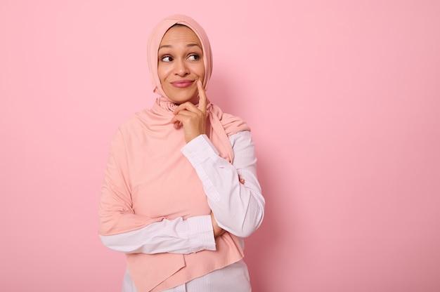 ヒジャーブで覆われた頭を持つ愛らしい若いイスラム教徒のゴージャスな美しい女性は、コピースペースのあるピンクの背景を不思議に見て、彼女の唇の隅に指を置き、思慮深く笑っています