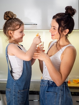 Adorable young sharing orange juice with mother