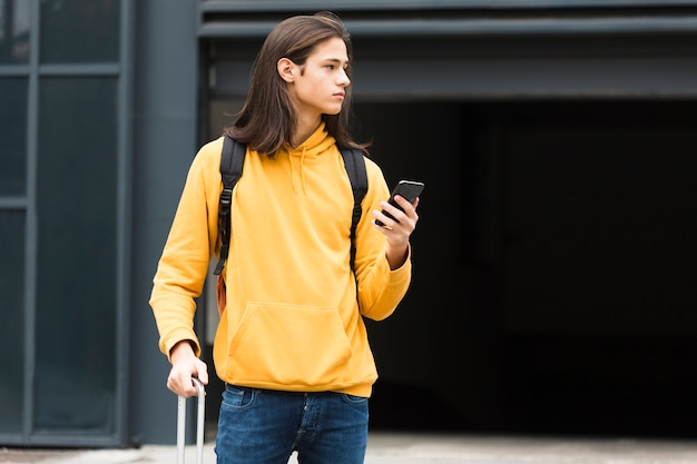 Adorable young traveler holding his phone