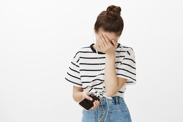 Adorable young woman in earphones, holding smartphone, laughing and facepalm while chuckle from joke