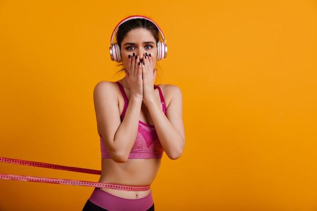 Adorable young woman in headphones measuring her waistline