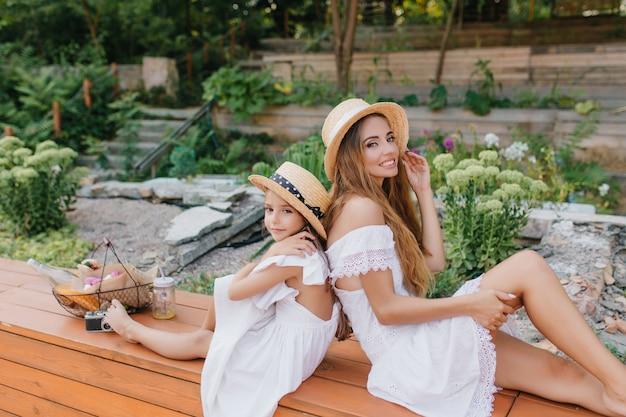 石と花のある美しい公園で楽しんでいる気分の良い愛らしい若い女性。トレンディなカンカン帽の母親の近くに座っているオープンバックのドレスを着た少女の屋外の肖像画。