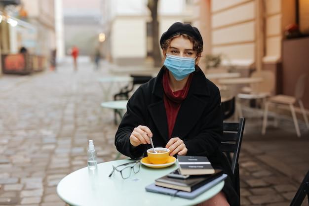 テーブルの上にコーヒーと消毒剤のカップとカフェテラスに座っている医療マスクの愛らしい若い女性。コロナウイルスと保護の概念。