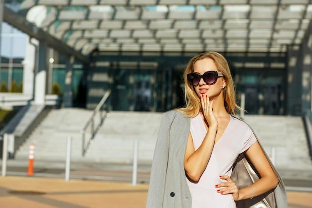 분홍색 드레스와 회색 재킷을 입은 세련된 안경을 쓴 사랑스러운 젊은 여성. 텍스트를 위한 공간