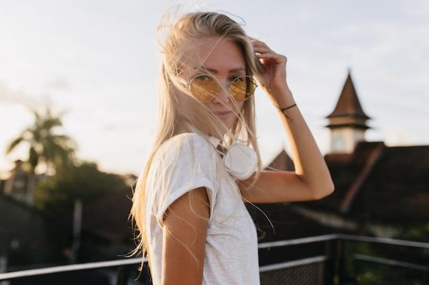 空の背景にポーズをとって黄色のサングラスで愛らしい若い女性。