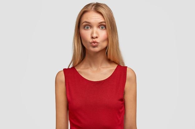 愛らしい若い女性は唇を丸く保ち、彼氏にキスをし、目を大きく開き、赤いファッショナブルな服を着ています