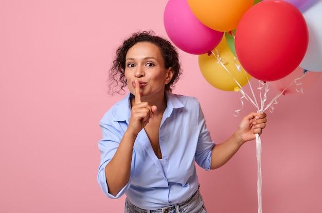 背中の後ろに気球がある混血民族の愛らしい若い女性は、人差し指を唇に当て、chutを身振りで示します。コピースペースとピンク色の背景に分離されたサプライズの概念