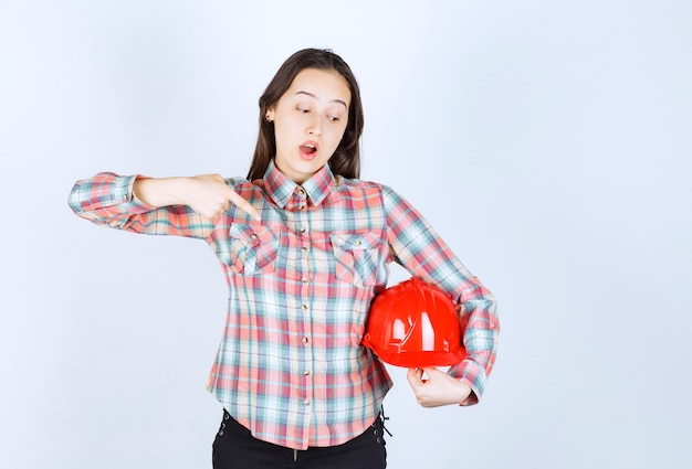 Adorable young woman pointing at red helmet on white background.
