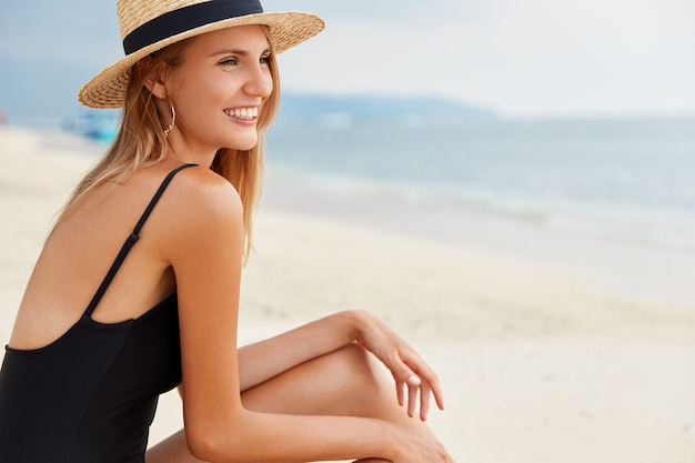Adorable young woman wears straw hat, sits on desert seashore alone, faces blue calm water, remembers some pleasant moments, has happy expression, likes to explore landmarks and marine beauties