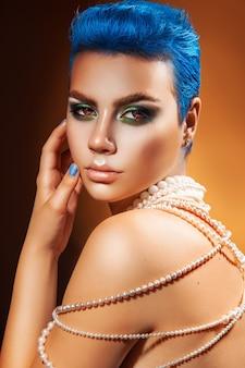 カメラを見て青い髪と爪を持つ愛らしい若い女性