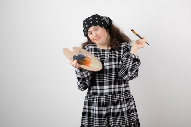 다운 증후군이 있는 사랑스러운 젊은 여성이 화가 팔레트를 들고 있습니다.