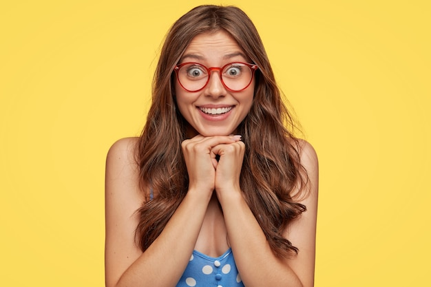 Adorable young woman with glasses posing against the yellow wall