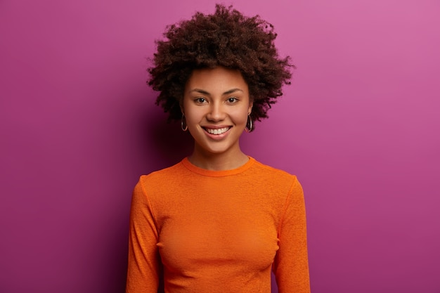 Adorable young woman with natural beauty, pleasant smile, loooks happily, smiles gently, wears orange poloneck, has curly bushy hair, isolated over purple wall. pleasant emotions concept