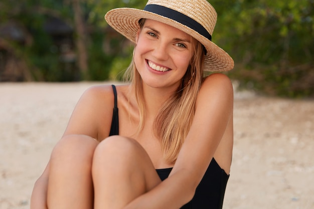 Adorable young woman with pleased expression, sunbathes on beach, sits on sandy beach, wears summer straw hat and black swimming suit, has tanned skin.