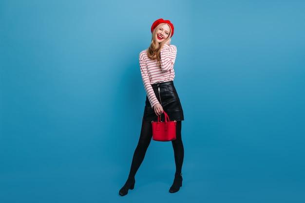 赤いハンドバッグを持つ愛らしい若い女性。青い壁に立っている気さくなフランス人女性。