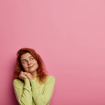 波状の赤い髪の愛らしい若い女性は、上を見て、ボーイフレンドが彼女にキスした方法を思い出し、顔の近くで手をつないで、微笑み、緑のジャンパーを着ています