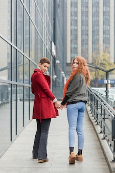 Adorable young women holding hands