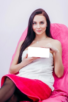 Adorable youngwoman holding box with empty space you can place you text or logo