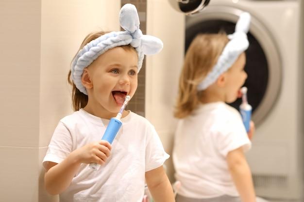 Очаровательный эмоциональный ребенок в синем изгибе головы, широко открывающий рот и держащий зубную щетку в ванной. biege фон. концепция гигиены.