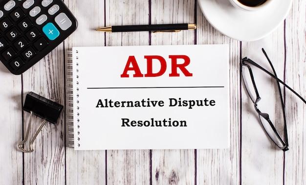 Adr裁判外紛争解決は、電卓、コーヒー、眼鏡、ペンの近くの白いメモ帳に書かれています。ビジネスコンセプト