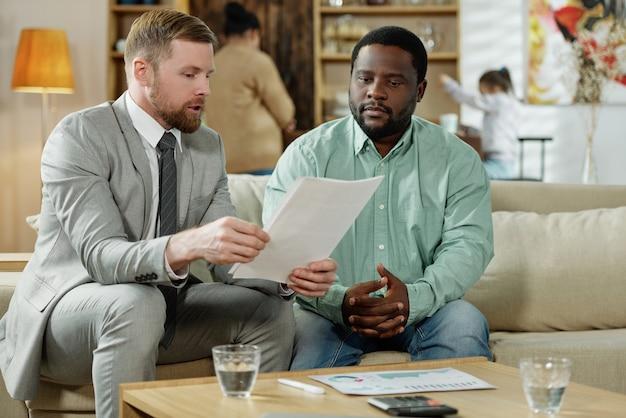 주택 융자에 대한 서류를 읽는 금융 컨설턴트와 함께 소파에 앉아 성인 아프리카 계 미국인 남자