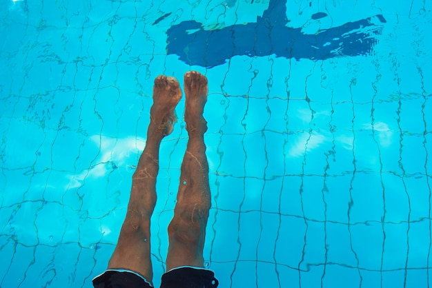 Adult african american mans legs underwater in swimming pool