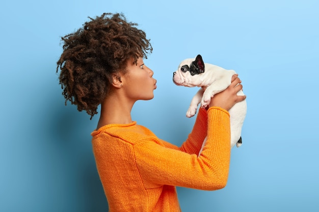 Adult afro girl stands in profile, raises little puppy in air