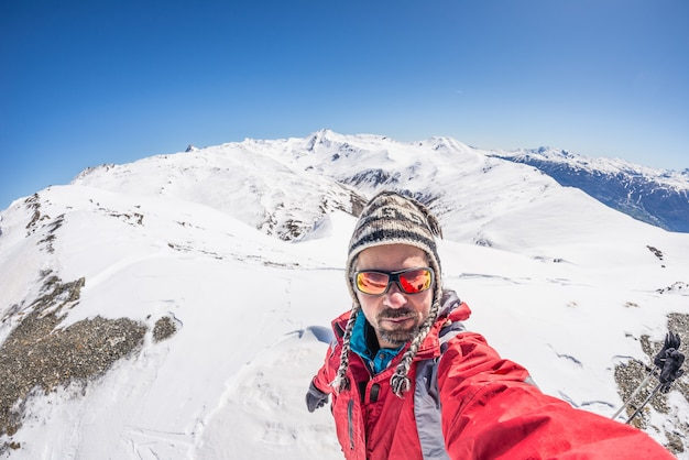 Adult alpin skier with beard, sunglasses and hat, taking selfie on snowy slope in the beautiful italian alps with clear blue sky. concept of wanderlust and adventures on the mountain