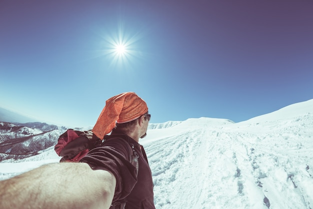 Adult alpin skier with beard, sunglasses and hat, taking selfie on snowy slope in the beautiful italian alps with clear blue sky. toned image, vintage style, ultrawide angle fisheye lens.