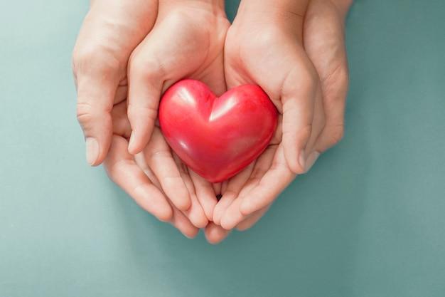 赤いハート、心臓の健康、寄付、幸せなボランティアチャリティー、csrの社会的責任、世界の心の日、世界の健康の日、世界の精神の健康の日、里親を保持している大人と子供の手