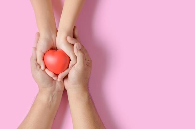 ピンクに分離された赤いハートを保持している大人と子供の手