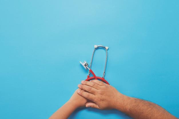 赤い聴診器を保持している大人と子供の手