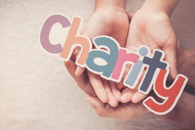 単語チャリティー、寄付、慈善の概念を保持している大人と子供の手