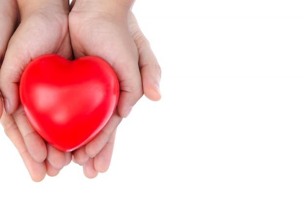 赤いハートを持っている大人と子供の子供の手。
