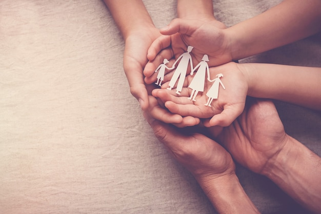 Руки взрослых и детей, держа бумаги семьи вырез