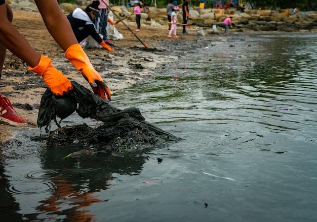 Взрослые и дети-добровольцы собирают мусор на морском пляже.