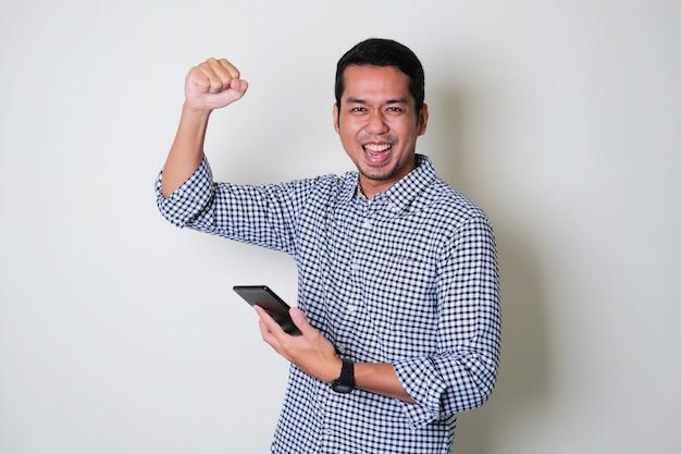 大人のアジア人男性は、モバイルタブレットガジェットを持って拳を空中に握りしめました。成功したコンセプト