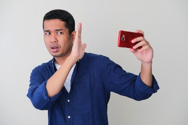 大人のアジア人男性が携帯電話に近づかないように顔を手で覆っている