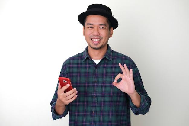 大人のアジア人男性が携帯電話を持っているときにokの指のサインを与える