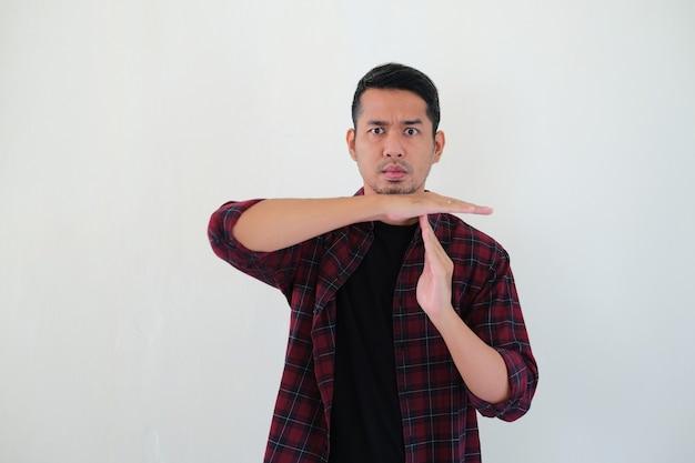 심각한 얼굴 표정으로 시간 초과 손 기호를주는 성인 아시아 남자
