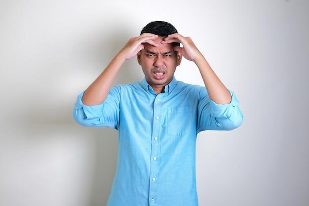 성인 아시아 남자는 고통스러운 두통 제스처를 얻었다