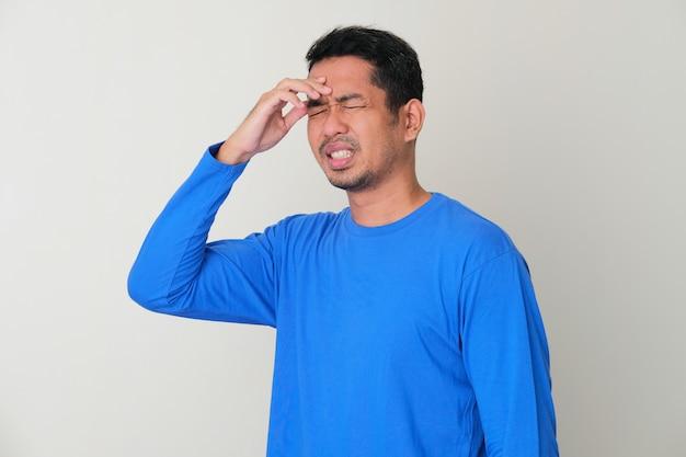 성인 아시아 남자는 고통스러운 편두통 제스처를 얻었다