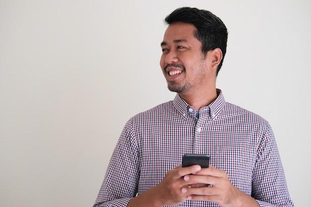 옆에 친절하게 미소 짓는 동안 휴대 전화를 들고 성인 아시아 남자