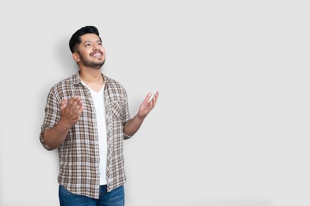孤立した背景の上の大人のアジア人男性は、攻撃的な表情と腕を上げてクレイジーで幸せな叫びと叫び声を上げます。幸せなコンセプト。